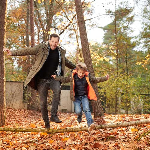 Father and son in autumnal forest at Center Parcs