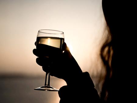 Brasserie - zonsondergang met silhouet van vrouw met wijnglas