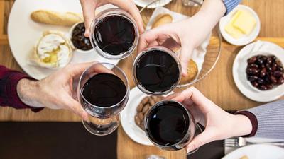 Brasserie Wine Bar – vier Freunde mit Rotweingläsern