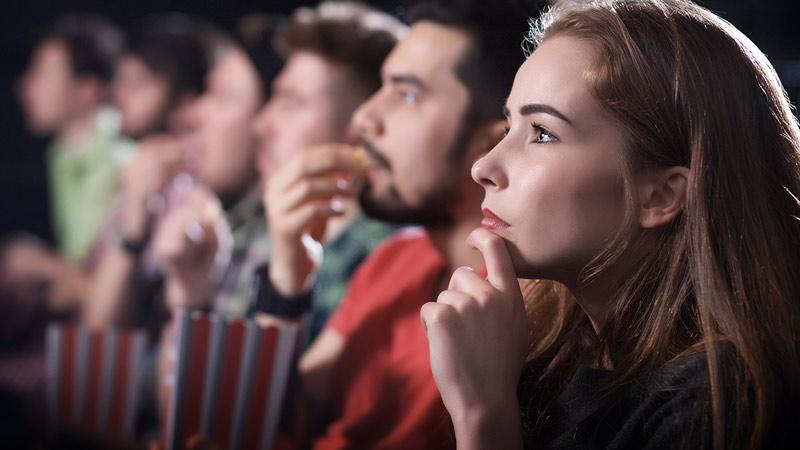 Bioscoop - rij mensen met popcorn die naar een film kijken