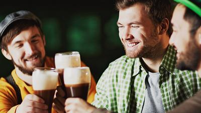 Irish pub - drie mannen die pinten bier drinken in een bar