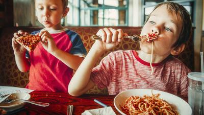 Kids' dinner time - two children eating spaghetti