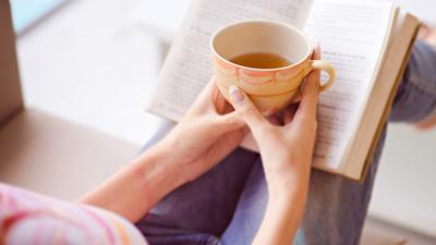 Ruhebereich – Frau liest ein Buch mit einer Tasse Tee