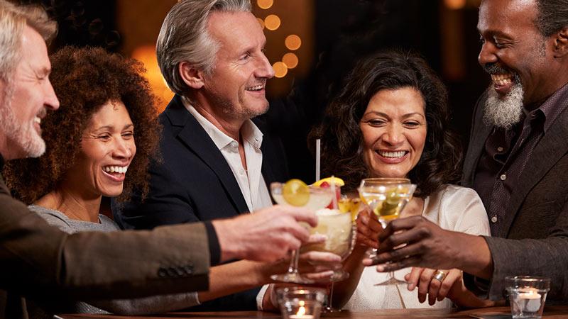 Sunset Show Bar - groep mannen en vrouwen van middelbare leeftijd die genieten van cocktails in een bar