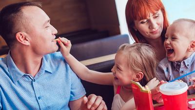 Family Lounge – junge Familie isst und albert in einer Nische