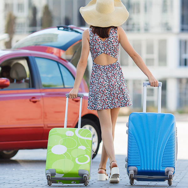 Passenger information - Woman with suitcases walking towards car